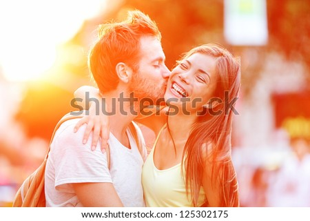 Couple kissing happiness fun. Interracial young couple embracing laughing on date. Caucasian man, Asian woman on Manhattan, New York City, USA.