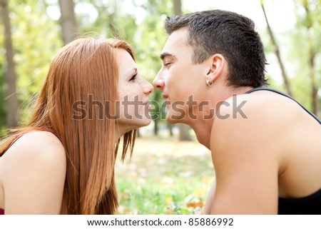 couple kissing on romantic date in park