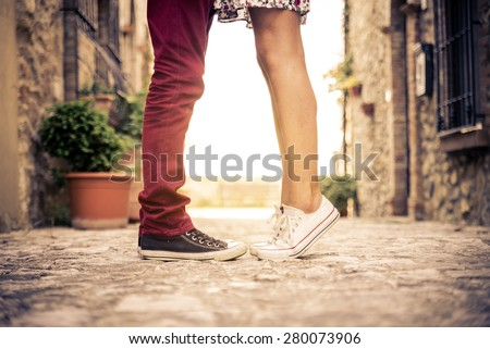 Couple kissing outdoors - Lovers on a romantic date at sunset,girls stands on tiptoe to kiss her man - Close up on shoes