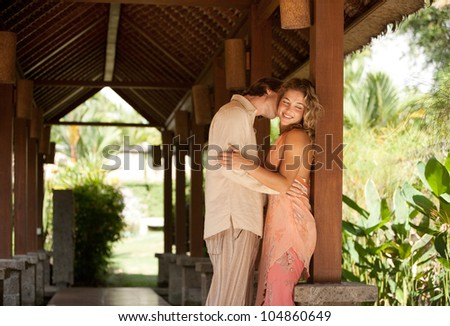 Couple kissing under a wooden structure in a tropical garden while on holiday.