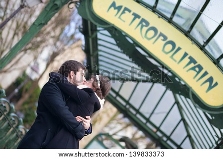 Couple kissing under the metro sign in Paris