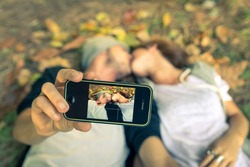 Couple kissing while taking a selfie with smart phone - autumn,people,love,technology,lifestyle concept