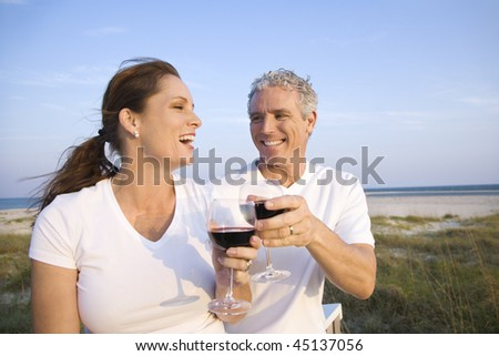 Couple laugh and drink wine on beach. Horizontal shot.