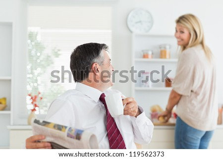 Couple laughing toghethe in kitchen before work with man holding mug and newpaper