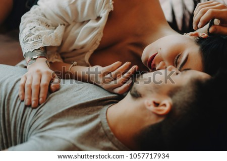 Couple laying on bed and hugging each other.