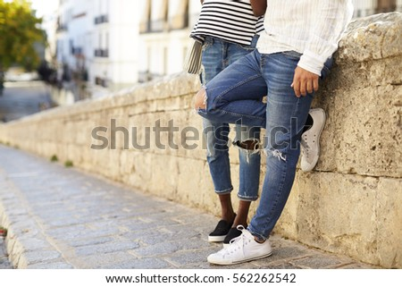 Couple leaning against a wall in Ibiza, Spain, low section