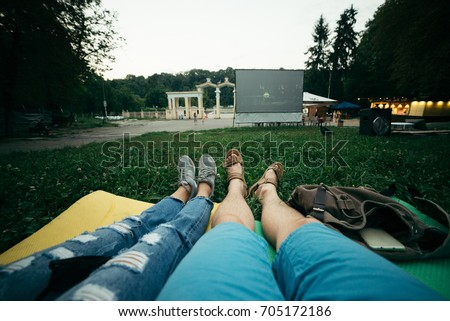 Shutterstock couple lies on the ground and watch movie in open air cinema first person view