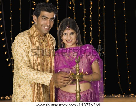 Couple lighting oil lamp on Diwali festival - stock photo