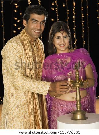 Couple lighting oil lamp on Diwali festival