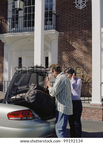 Couple loading trunk of car