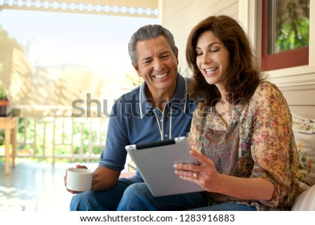 Couple looking at an ipad on their verandah.