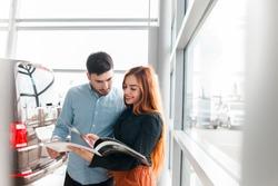 Couple looking at car dealership catalog