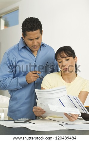 Couple looking at documents while preparing financial budgets