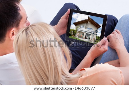 Couple Looking At House On Digital Tablet\'S Screen