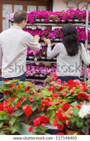 Couple looking at shelf of purple flowers in garden center
