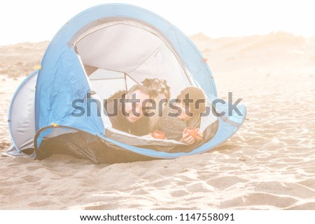 couple looking at the smart phone and have fun inside a tent in free camping on the beach Dog border collie behind them looking at the camera. vintage colors and vacation family concept.