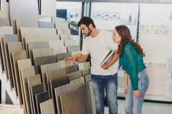 Couple looking ceramic and tiles for their new home floor. They are choosing in furnitures store