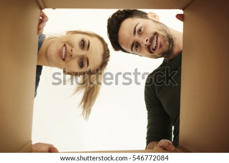 Couple looking down at camera through cardboard box 