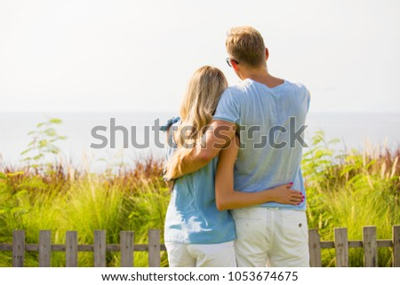 Couple looking into distance, shot from behind