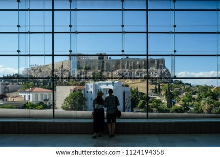 Couple looking out at the Acropolis throught huge glass window in the Acropolis Museum. Athens, Greece.