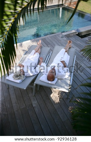 Couple lounging by a pool