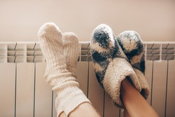 Couple love. Legs with socks on heating radiator. Couple. Romantic lovers.