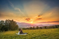 couple, love, nature and people concept - happy loving couple sitting on a plaid in a field on a background of magical sunset