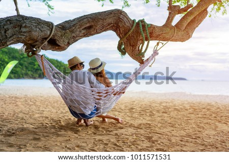 couple lover enjoy honeymoon and long vacation on the sea beach, siiting on the swing together relax and confortable, valentine occasion #1011571531