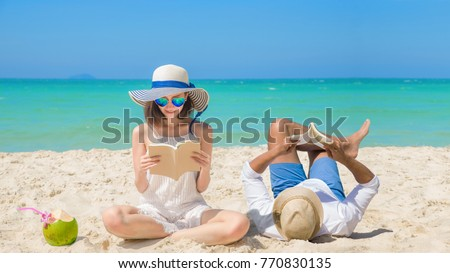 couple lover happy reading a book and enjoy drinking fresh coconut by laying & sitting down on the sand beach, with cleared blue sea & sky in background