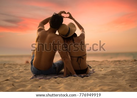 Couple lover make hand lover on the sunset beach