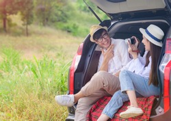 couple lover sitting back cap of the car, enjoy taking photo together on trip traveling