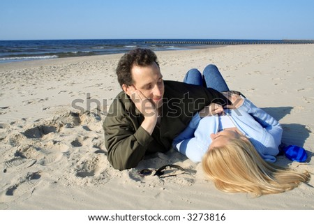 Couple lying down on a beach