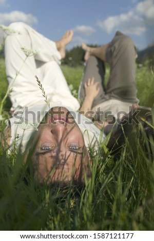 Couple lying in a field, man looking back towards camera