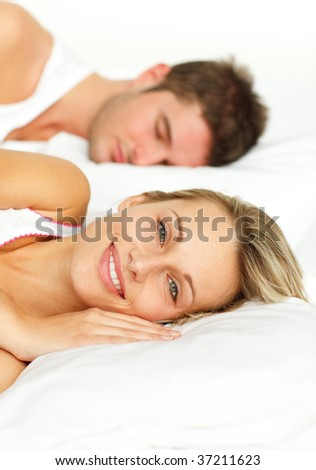 Couple lying in bed. Man sleeping and woman smiling at the camera