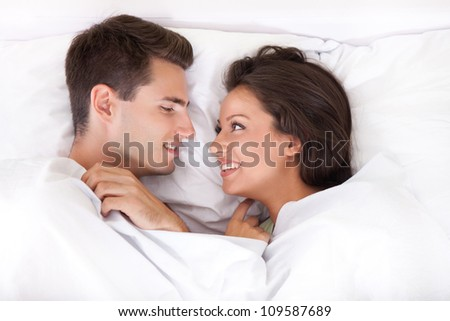 Couple lying in bed smiling at each other