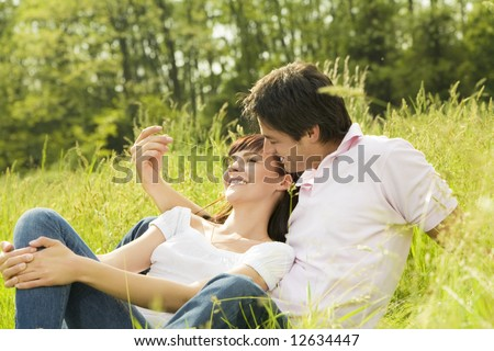 Couple lying in grass, man tickling her girlfriend's nose and smiling