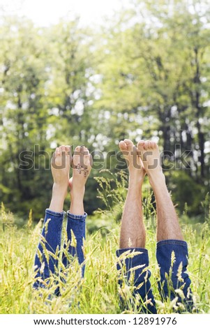 Couple lying in grass stretching their legs up