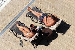 Couple lying in lounge chairs and sunbathing near the swimming pool, top view. Woman in swimsuit and man in trunks using smartphones on a beach, family holiday and vacation