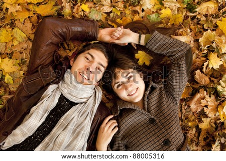 Couple lying in the park in fall.