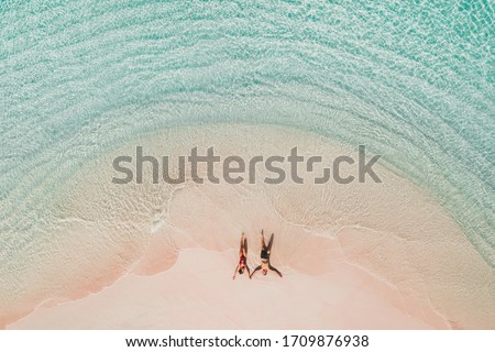 Couple lying on famous pink beach in Komodo national park. Turquoise mint color clear water, tropical vacations on honeymoon. Drone aerial view from above. Stockfoto ©