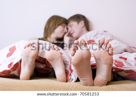 Couple lying on the bed barefoot