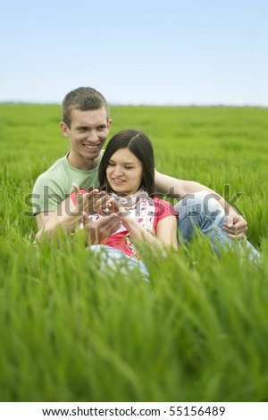 Couple lying on the grass and communicates - stock photo