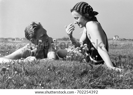 couple lying on the grass in...