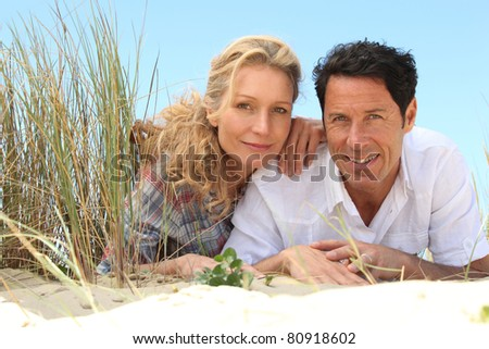 Couple lying on the sand.