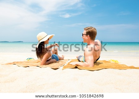 Couple lying on white sand beach relaxing and taking a sunbath in summer at Koh samui island, Thailand #1051842698