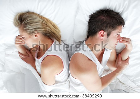 Couple lying separately in bed after having a fight. Marriage trouble