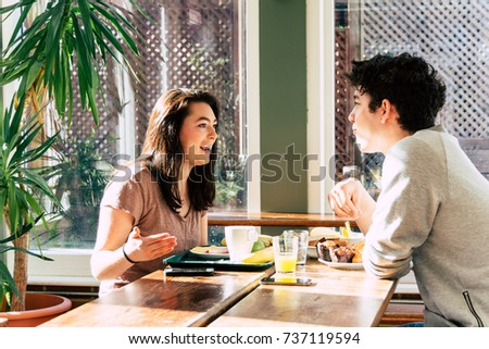 Couple making breakfast time in hostel and speaking about funny moments. Boyfriend and girlfriend doing lunch in self service restaurant. Concept of best friends having fun. People during day life. #737119594