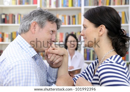 couple making up at therapy session with psychologist - stock photo