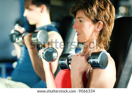 Couple (male / female) lifting dumbbells in a gym; focus on face of the woman - stock photo