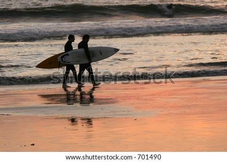 Couple male surfers walking along the beach at sunset